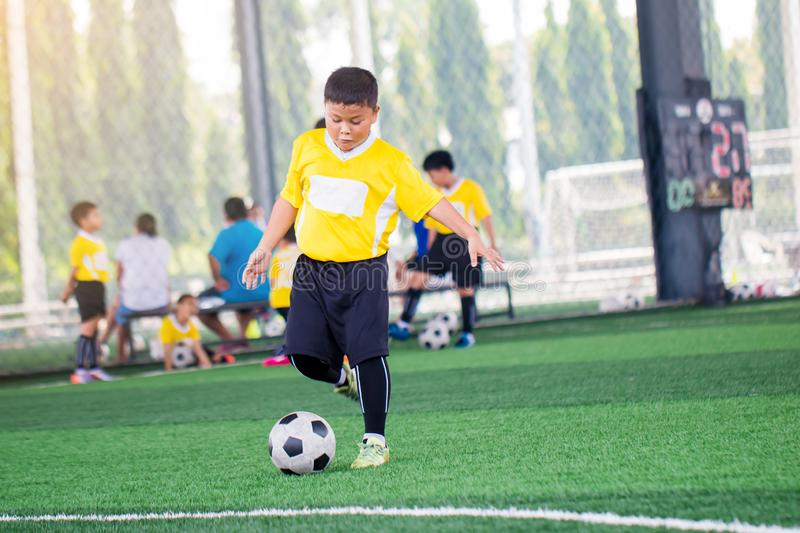 Blurry ball with Asian kid soccer player speed run to shoot ball to goal on artificial turf. Kid soccer player training or football match. Asian boy soccer royalty free stock image