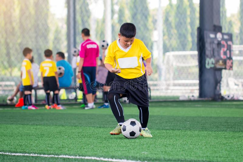 Blurry ball with Asian kid soccer player speed run to shoot ball to goal on artificial turf. Kid soccer player training or football match. Asian boy soccer stock photo