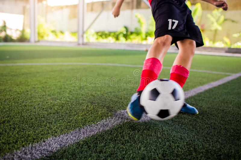 Blurry ball after boy soccer player speed run on green artificial turf to shoot it to goal royalty free stock images