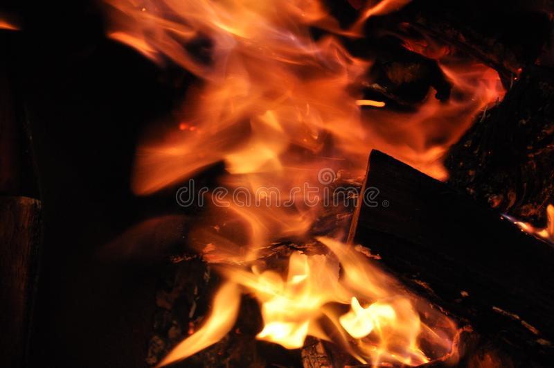 Blurry bonfire is blazing. Burning fire texture. Abstract flame blurred motion on black background. Fiery flames in darkness. royalty free stock image