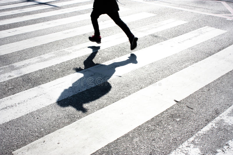 Blurry child and its shadow on zebra crossing stock photos
