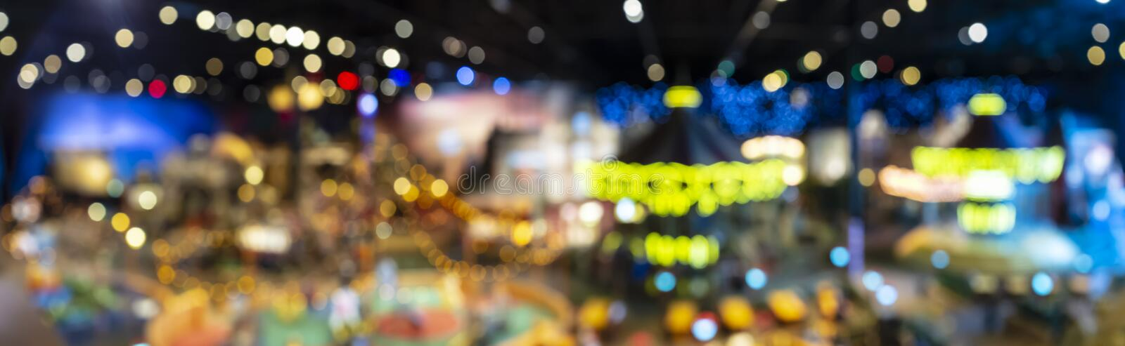 Blurry and defocused multicolored lights of the carousel in the night park. Panorama royalty free stock image