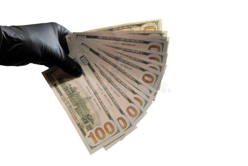blurry Die linke Hand in einem schwarzen Handschuh hält Dollarscheine Weißer Hintergrund Kopieren Sie Platz lizenzfreie stockfotos