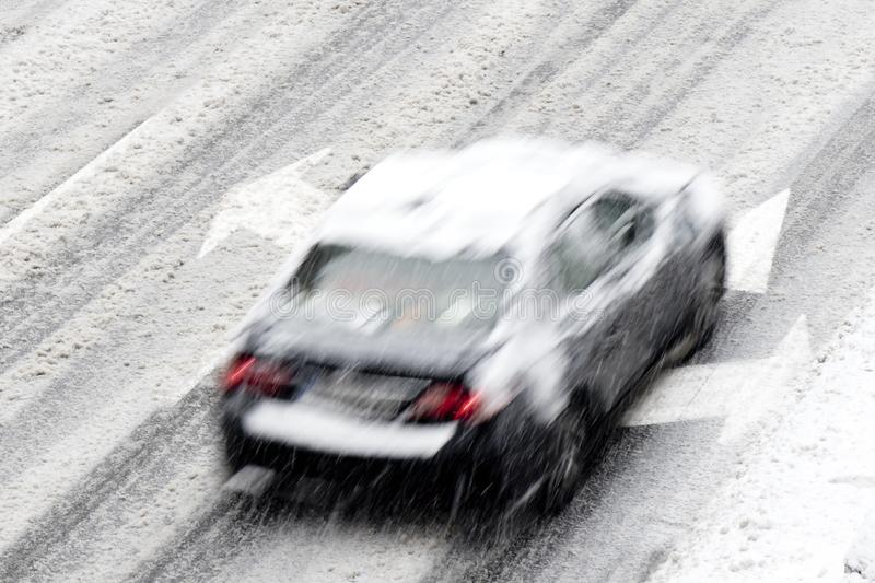 Blurry driving car on the empty city street with arrow street markings on a snowy day royalty free stock photography