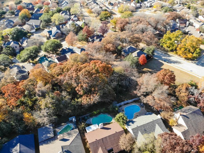 Blurry drone view residential houses with garden, garage and colorful leaves near Dallas. Blurred aerial view residential neighborhood with colorful fall foliage stock images