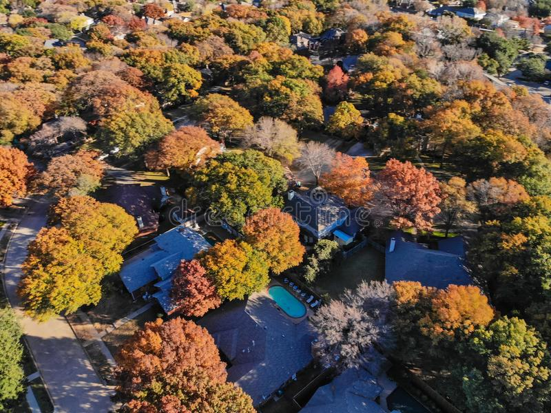Blurry drone view residential houses with garden, garage and colorful leaves near Dallas. Blurred aerial view residential neighborhood with colorful fall foliage stock photography