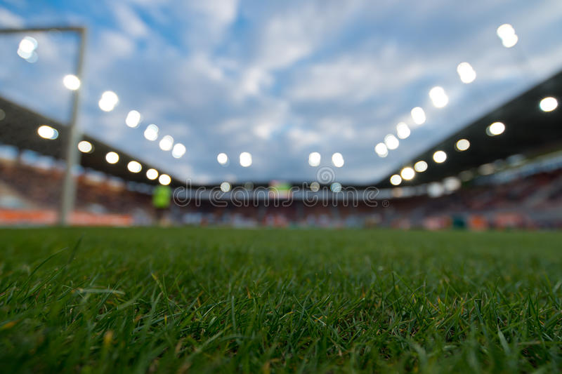 Blurry football stadium. Blurry football stadium, grass in the focus royalty free stock photo
