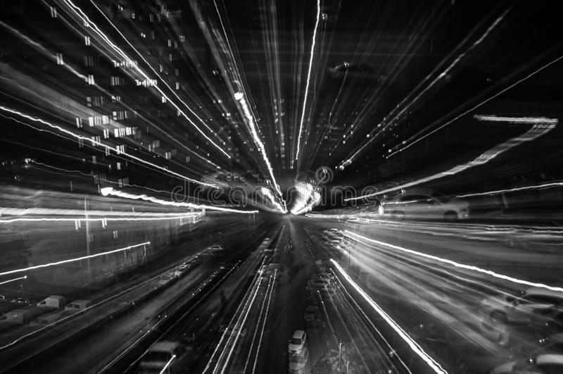 Blurry glare of the night city. Background for a dynamic picture. Black and white frame.  royalty free stock photo