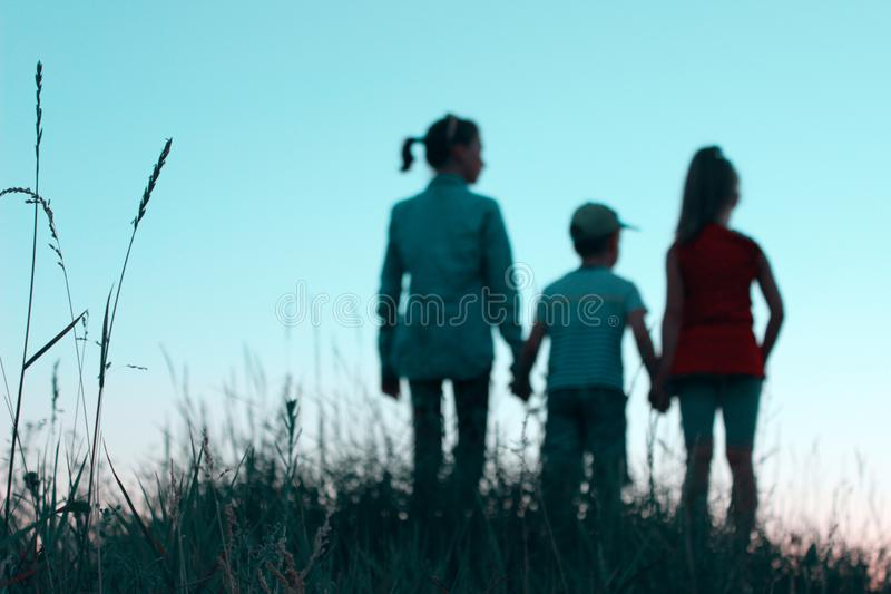 Blurry image of children standing in a clearing holding hands. People, children, childhood and family concept. royalty free stock photo