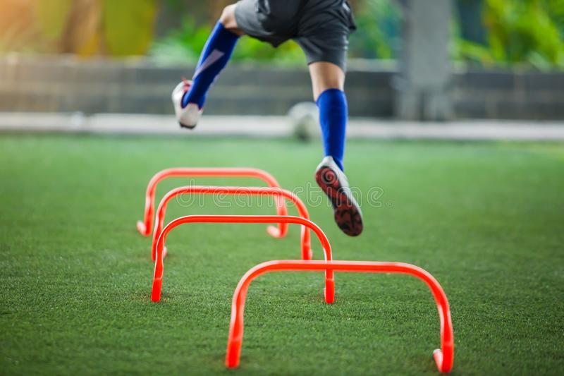 Soccer player jogging and jump between marker for football training with blurry other players waiting to follow him. stock photos