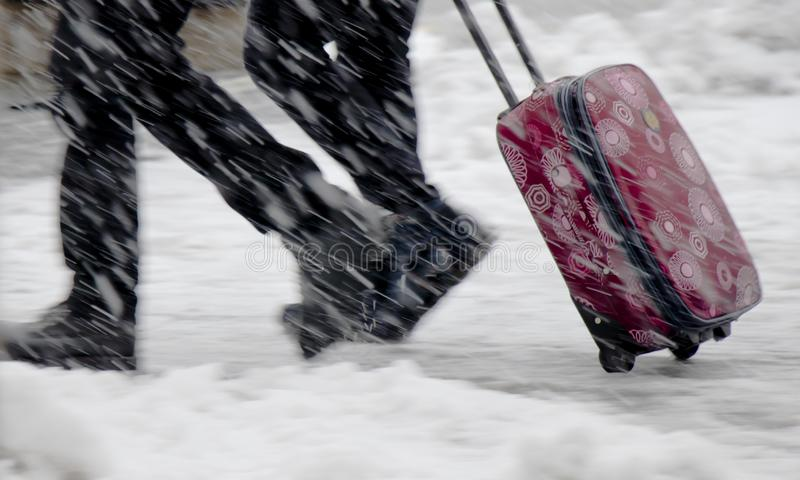 Blurry legs of two people walking fast in heavy snowfall and rolling red suitcase royalty free stock image
