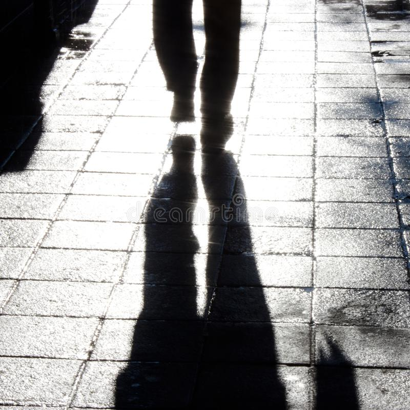 Blurry man legs walking city street. Defocused silhouette and shadow of one man`s legs walking alone on wet city street with reflection and blur after the rain stock image