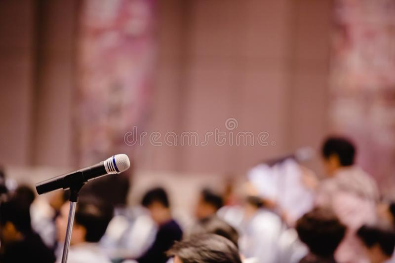 Blurry of microphone in auditorium and projector for shareholders ` meeting. Or seminar event stock photography