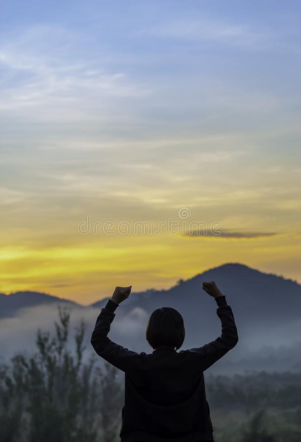 Blurry morning sun light behind the mountains and Women raise their arms stock photography