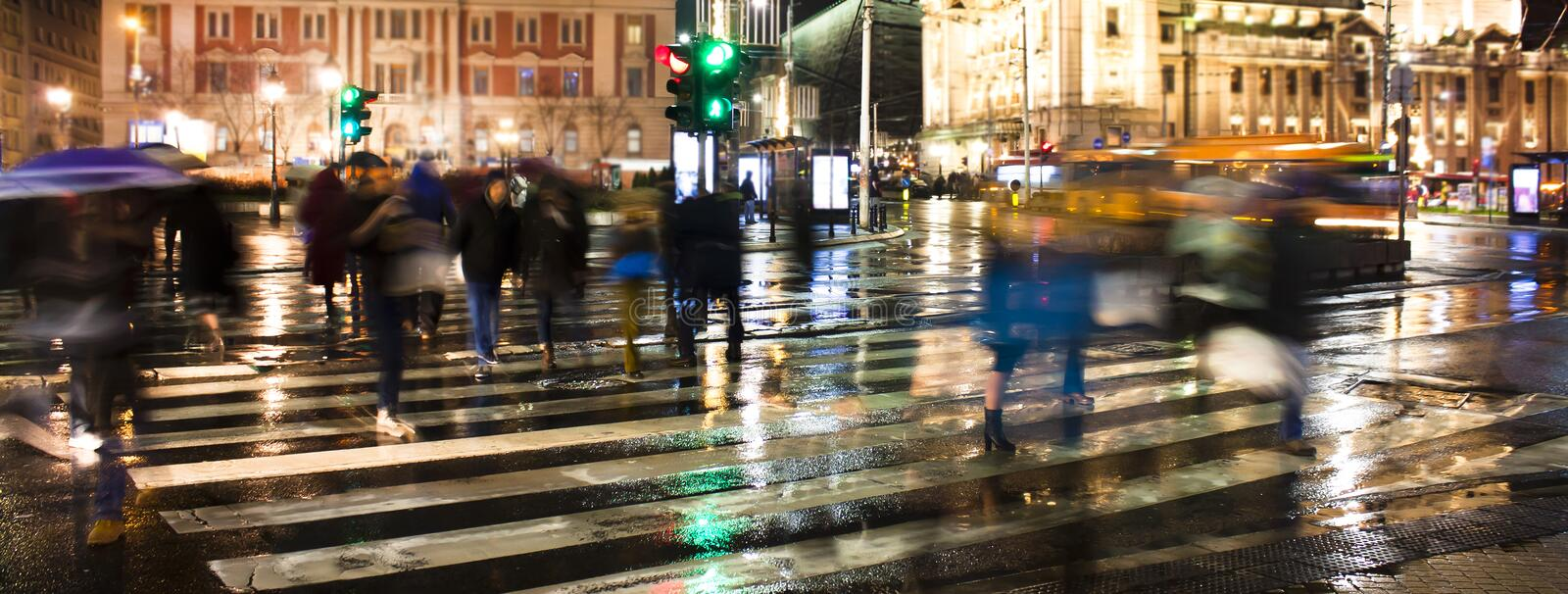 Blurry people crossing the city street in rainy night royalty free stock image
