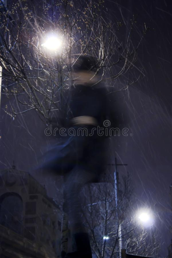 Blurry person walking alone in snowy city night. Blurry person walking alone in snowy and windy city streets in winter night , low angle view stock photo