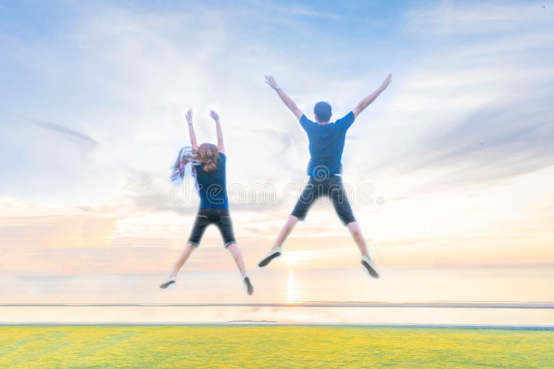 Blurry photo of couple jumping on the beach royalty free stock image