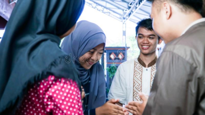 Blurry portrait close up shot of Muslim couples visiting their family or friend home while shaking hand and hugs on eid mubarak royalty free stock images