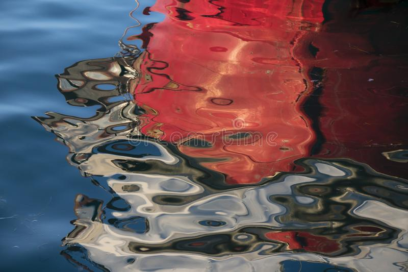 Blurry reflection of red boat bow. In the sea stock image