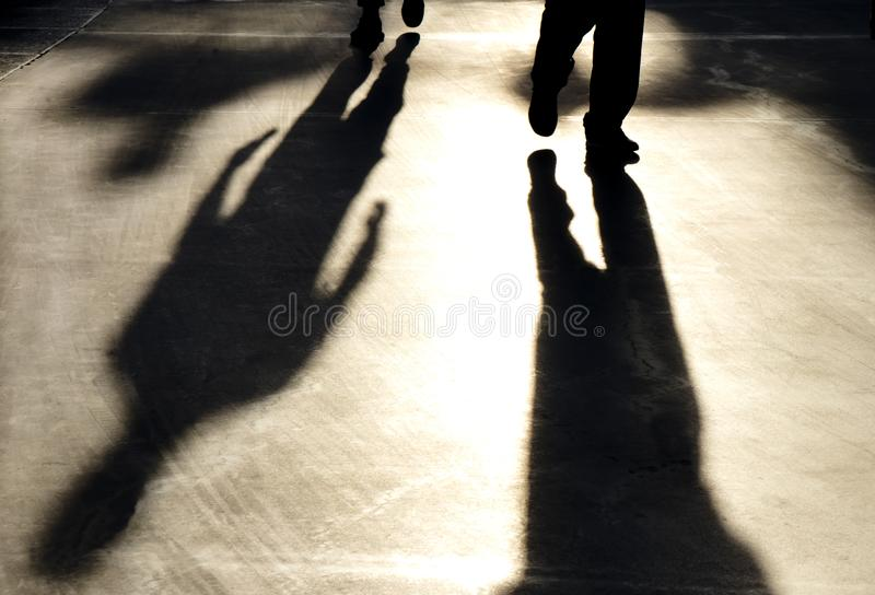 Blurry reflection shadow silhouette of  men walking on pedestrian road. In sunset royalty free stock images