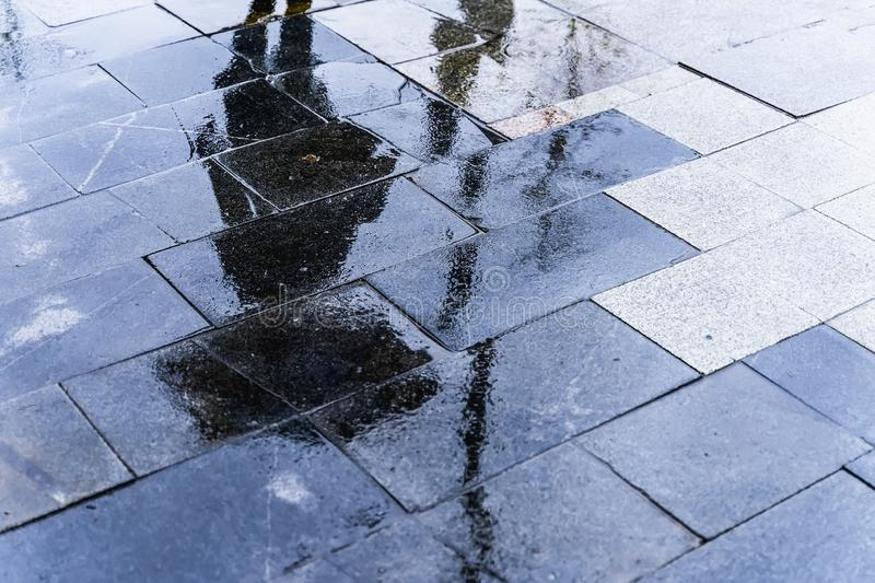 Blurry reflection shadow silhouette of a woman walking under umbrella in a pedestrian city wet street in a puddle royalty free stock photos
