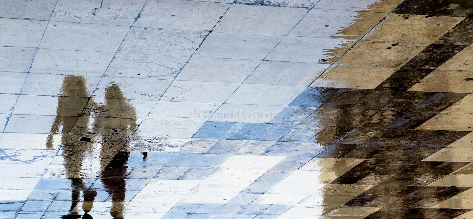 Blurry reflection shadow silhouettes of  two girl friends walking on a wet city street. Blurry reflection shadow silhouettes of  two girl friends walking on a royalty free stock images