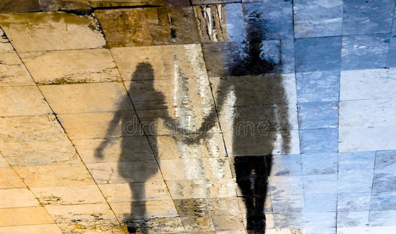 Blurry reflection shadow silhouettes of  a young couple walking on a rainy summer day. Blurry reflection shadow silhouettes of  a young couple walking on a wet royalty free stock images
