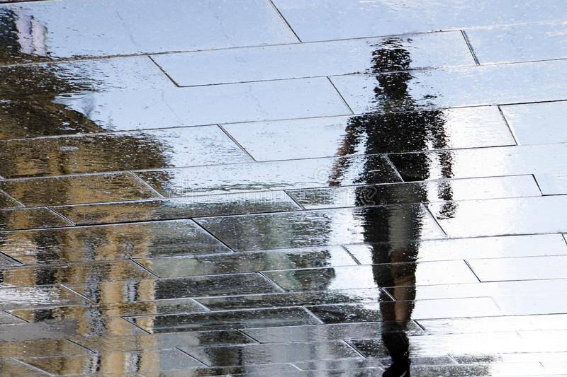 Blurry reflection silhouette of a person walking wet city stree royalty free stock images
