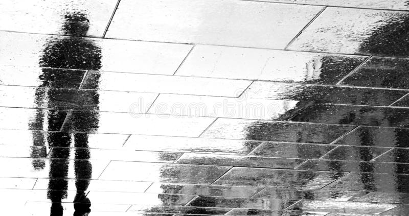 Blurry reflection silhouettes of a man walking on a rainy day royalty free stock photos