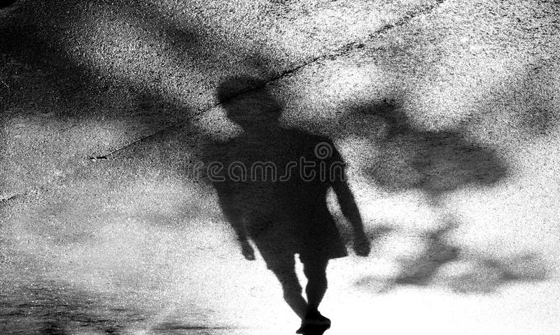 Blurry shadow silhouette of one young men walking alone  in high contrast black and white royalty free stock photo