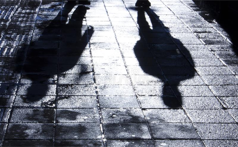 Blurry shadow and silhouette of two men standing in the night royalty free stock photo