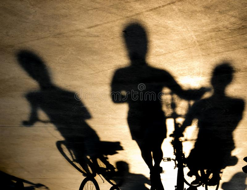 Blurry shadow of three young women on bikes stock images