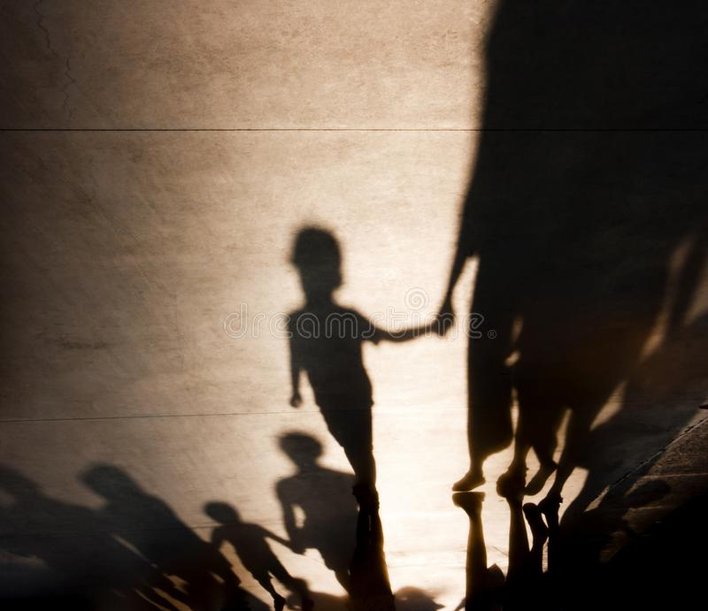 Blurry shadows of families with kids walking. Blurry shadows silhouettes of families with kids walking and holding hands on misty summer promenade royalty free stock images
