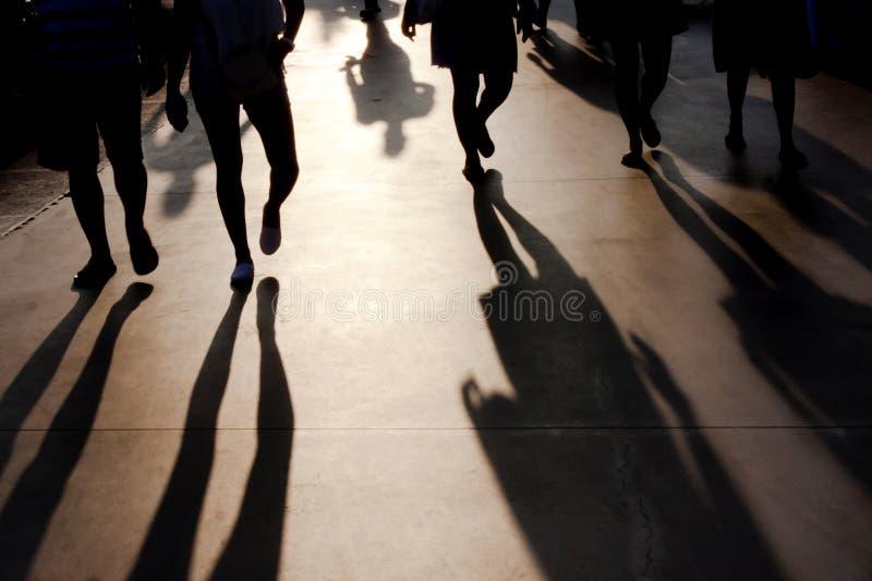 Blurry shadows of people walking on summer promenade stock photo
