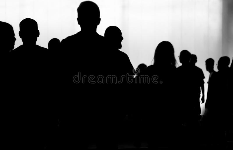 Blurry silhouette of crowd of young people walking m in the nigh. Blurry silhouette of crowd of young people walking in the night in black and white stock image