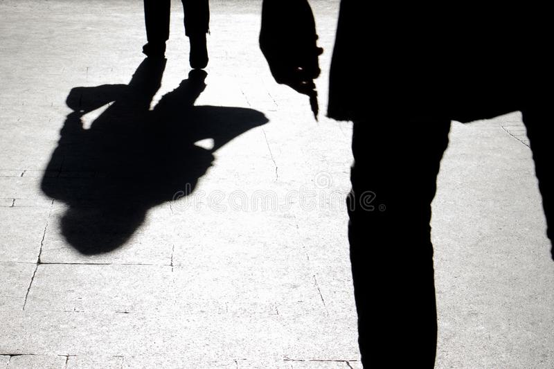 Blurry silhouette and shadow of a woman carrying a bag and a man. Holding sharp object following her, in the city street in the night stock photography