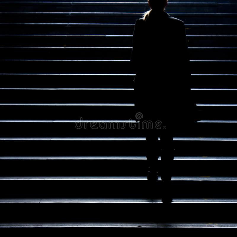 Blurry silhouette of young elegant woman climbing up the city st stock photography