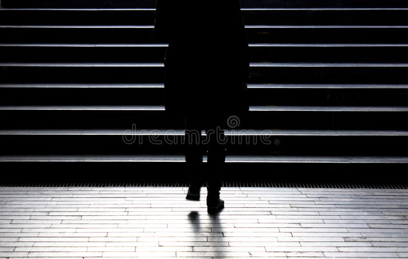 Blurry silhouette of young woman climbing up the city street sta stock image