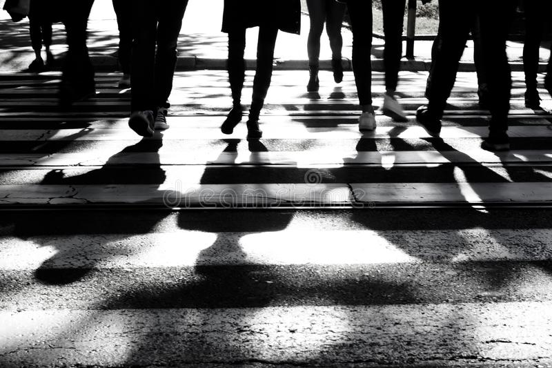 Blurry shadows and silhouettes of people on crossroad stock image