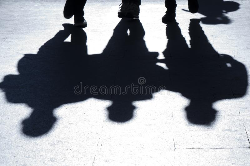 Blurry silhouettes and shadows of three people walking city street stock image