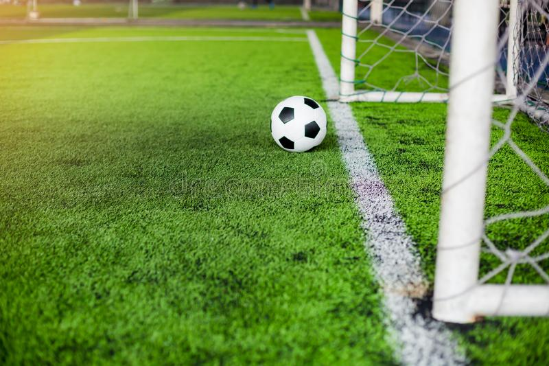 Blurry soccer ball on green artificial turf move to goal at front of the goal line stock photo