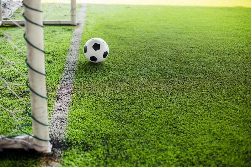 Blurry soccer ball on green artificial turf move to goal at front of the goal line stock photography