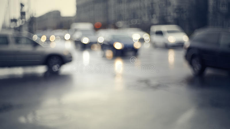 Blurry unfocused background with the city road with cars in twilight. After a rain. Out of focus city landscape in twilight after a rain stock photo