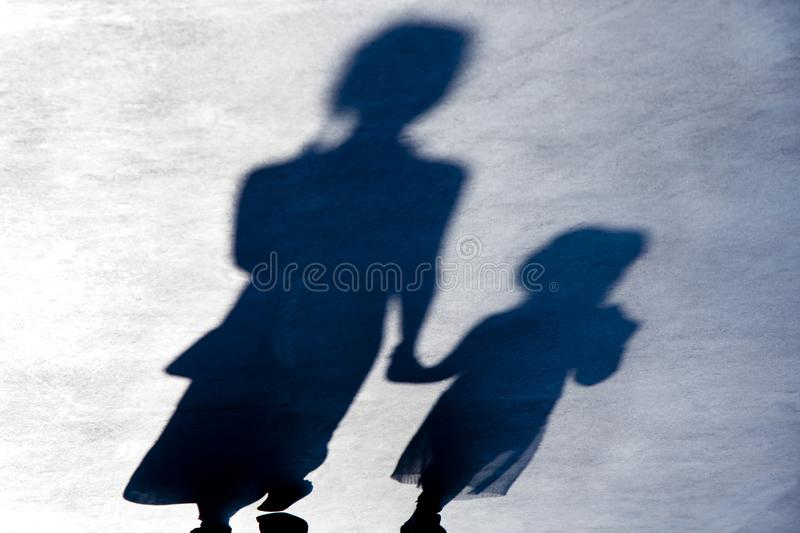 Blurry vintage shadows silhouettes of two person walking  in the night stock image