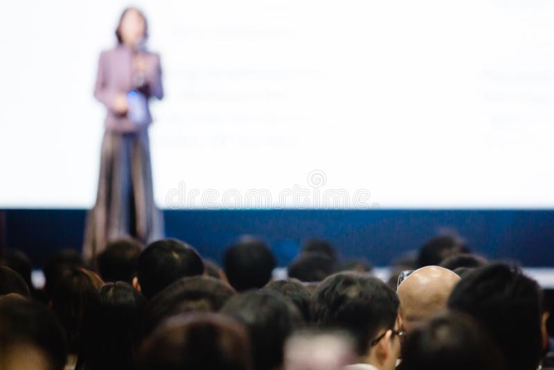 Blurry of woman speaker speech on stage in auditorium for shareholders` meeting royalty free stock photo