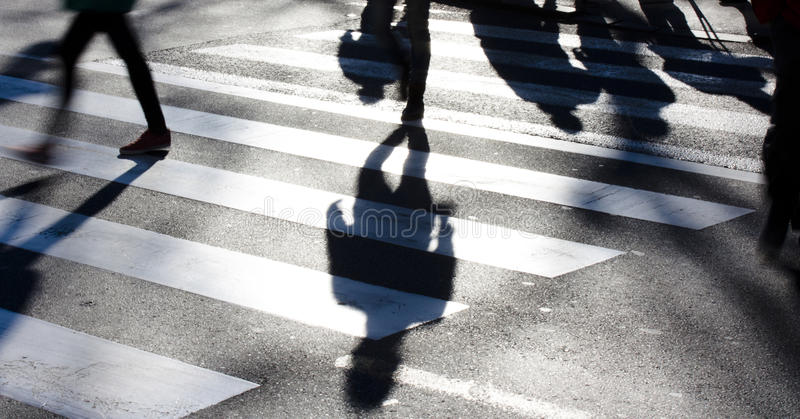 Blurry zebra crossing with pedestrians making long shadows. In the cold, windy and sunny winter in black and white royalty free stock image