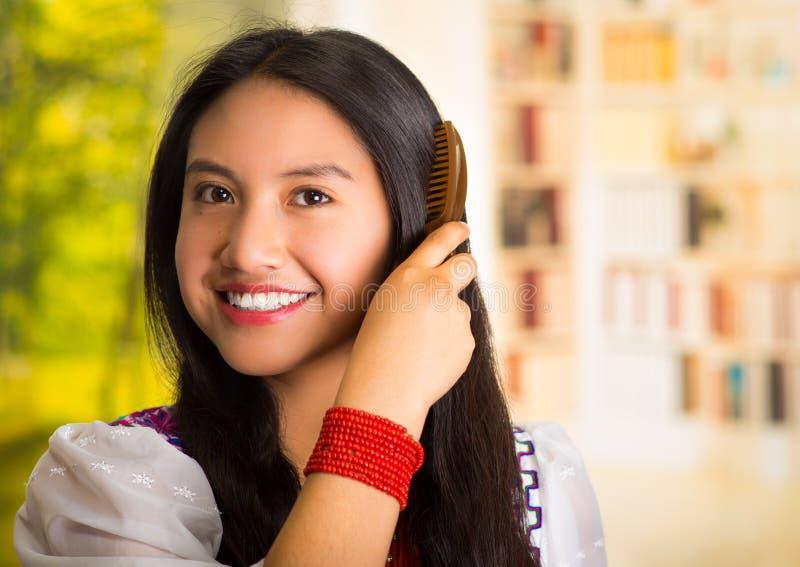 Blusa branca vestindo da mulher latino-americano bonita com bordado colorido, usando a escova de cabelo pequena durante a rotina  fotos de stock royalty free