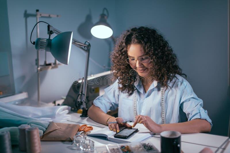 Blusa d'uso della donna ed avere messaggio di misurazione di scrittura del nastro all'amico all'interno fotografie stock
