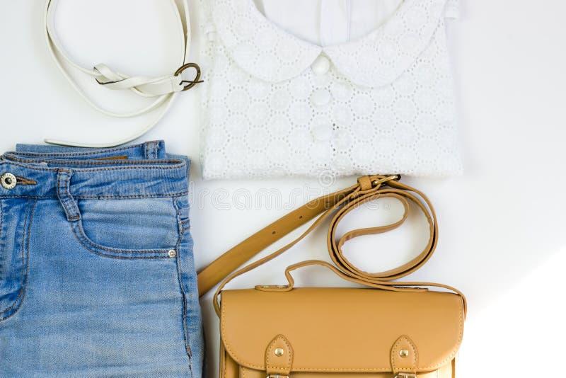 A blusa das mulheres brancas do laço, a calças de ganga, uma bolsa marrom e uma correia branca em um fundo branco Os equipamentos imagens de stock