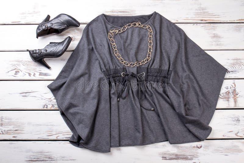 Blusa gris y zapatos negros del tacón alto, endecha plana imagen de archivo libre de regalías